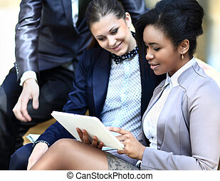 Businesswomen With Digital Tablet Sitting In Modern Office...