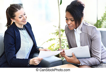 Businesswomen With documents and folder Sitting In Modern...