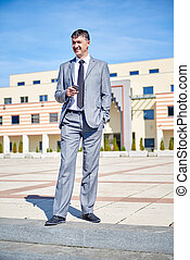portrait of middle aged business man standing outdoor on stairs