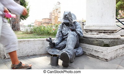 Busker earns living sitting on sidewalk, depicting stone...