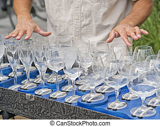 busker playing filled crystal glasses of water with fingers