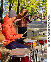 Buskers with girl violinist on autumn outdoor.