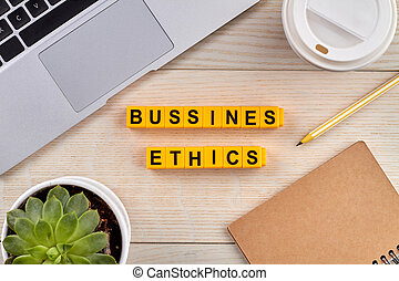 Bussines ethics concept. Tools for work and cup of coffee near the laptop on the desk. Yellow blocks on the wooden desk.