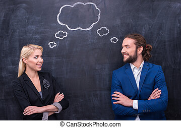 Male and female thinking together on th blackboard background