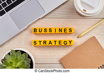 Bussines strategy concept. Words building with yellow cubes. Workplace with tools for work on background.