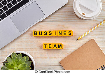 Bussines team concept. Words written with yellow letter blocks. Laptop with cup of coffee and pencil with notepad on the desk.