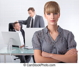 Businesswoman in his clean high tech office with associates in the background laughing