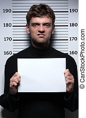 Busted burglar. Angry burglar holding a white poster while...