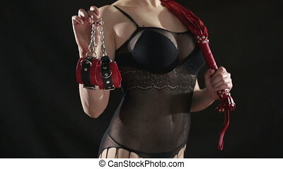 Busty girl in lingerie shows Red handcuffs. on black background. sex toy. red leather whip
