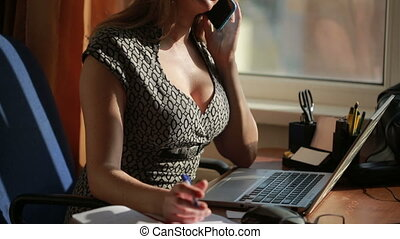 Busty sexy business woman working for a laptop. talking on the phone