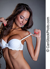 Busty tanned brunette dressed in white bra - Portrait of...