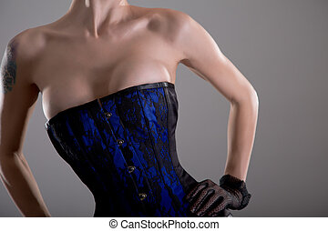 Busty young woman in black and blue corset with floral pattern