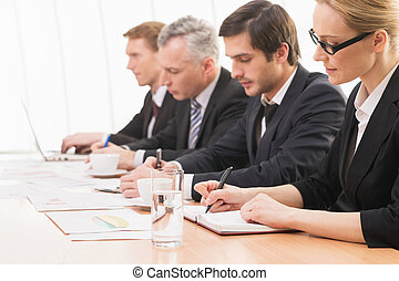 Busy and confident. Four people in formalwear working together while sitting at the table
