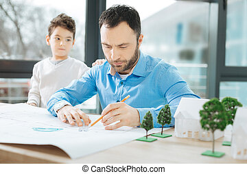 Busy architect paying no attention to his little son - Lack...