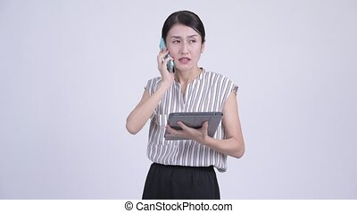 Busy Asian businesswoman talking on the phone and using digital tablet