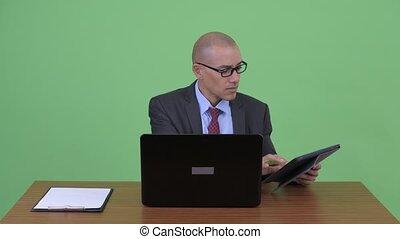 Busy bald multi ethnic businessman multitasking at work...