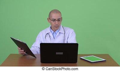 Busy bald multi ethnic man doctor multitasking at work...