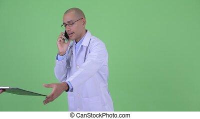 Busy bald multi ethnic man doctor multitasking at work -...