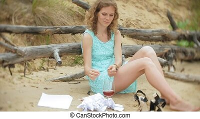 busy beautiful young woman working on a laptop computer with business papers picking up a phone to work a call sitting on the beach by the sea on a sunny day and drinking wine from a glass