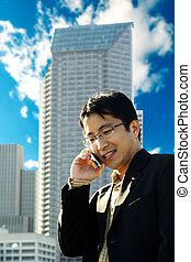 Busy businessman - A businessman talking on the phone at a...