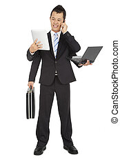 busy businessman holding mobile phone and laptop and tablet pc and briefcase