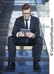 Busy businessman sitting on steps