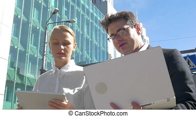 Busy businesspeople with electronics in the city