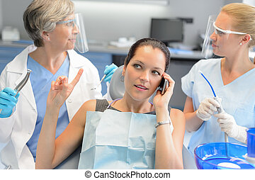Busy businesswoman at dental surgery on phone
