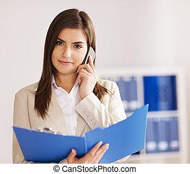 Busy businesswoman in talking on smart phone
