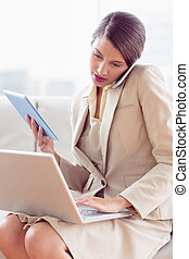 Busy businesswoman sitting on sofa multi tasking in the...