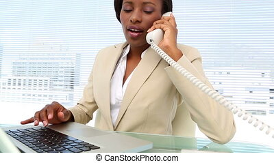 Busy businesswoman talking on phone and using laptop at desk...