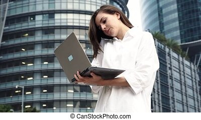 Busy businesswoman work on laptop computer and talking on phone