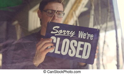 """Busy cafeteria waiter in apron is looking outside through glass door and changing doorplate from """"sorry we are closed"""" to """"yes we are open"""". Starting work day and business concept."""