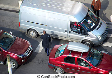 Busy city life - People crossing the road in traffic jam. ...