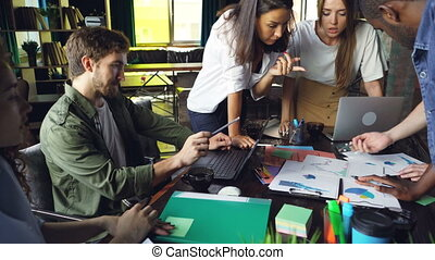 Busy colleagues are working with charts and graphs talking and sharing ideas in modern office with papers and laptops on table. Teamwork, youth and business concept.