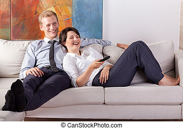 Busy couple watching tv after work