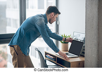 A young man working in the office and looking busy