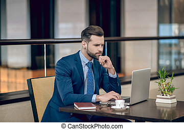 Young businessman in a nice suit working in the office and looking concentrated