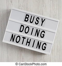 'Busy doing nothing' on a modern board over white wooden surface, top view. From above, flat lay, overhead.