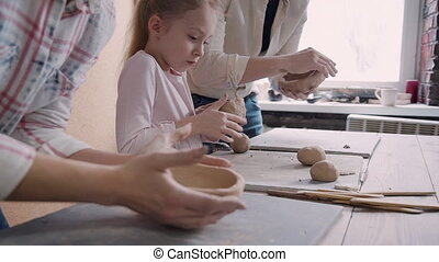 Busy family working with clay in pottery studio - Two adult...