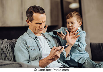 Busy father brushing away his son asking for attention