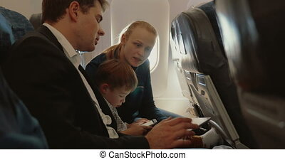 Busy father, child and mother traveling by plane