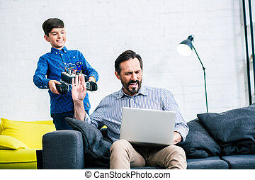 Busy father not paying enough attention to his son