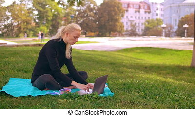 busy girl works and eats outdoors - young caucasian woman...
