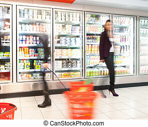 Busy Grocery Store - Blurred motion of people walking near...