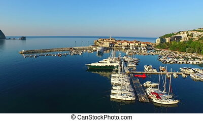 Busy harbor near the Adriatic sea with many small boats at anchor. Aerial view