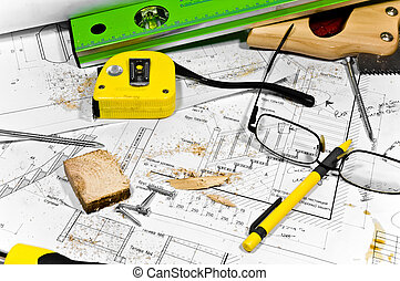 Busy hobby workbench. Different carpenter tools: saw, hummer, tape measure, level ruler, screwdriver are lying in the saw dust upon the blueprints and drawings along with screws, pencil and glasses.