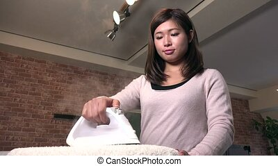 Busy Housewife Using Iron At Home For Daily Domestic Chores...
