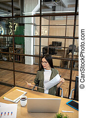 Long-haired brunette asian girl working in the office and looking busy