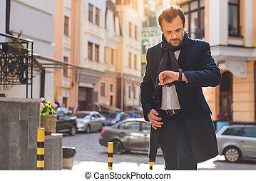 Busy man checking time while walking